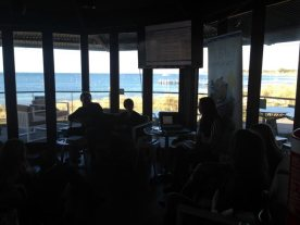 a panel session at Aristos with Thompson Bay in the background